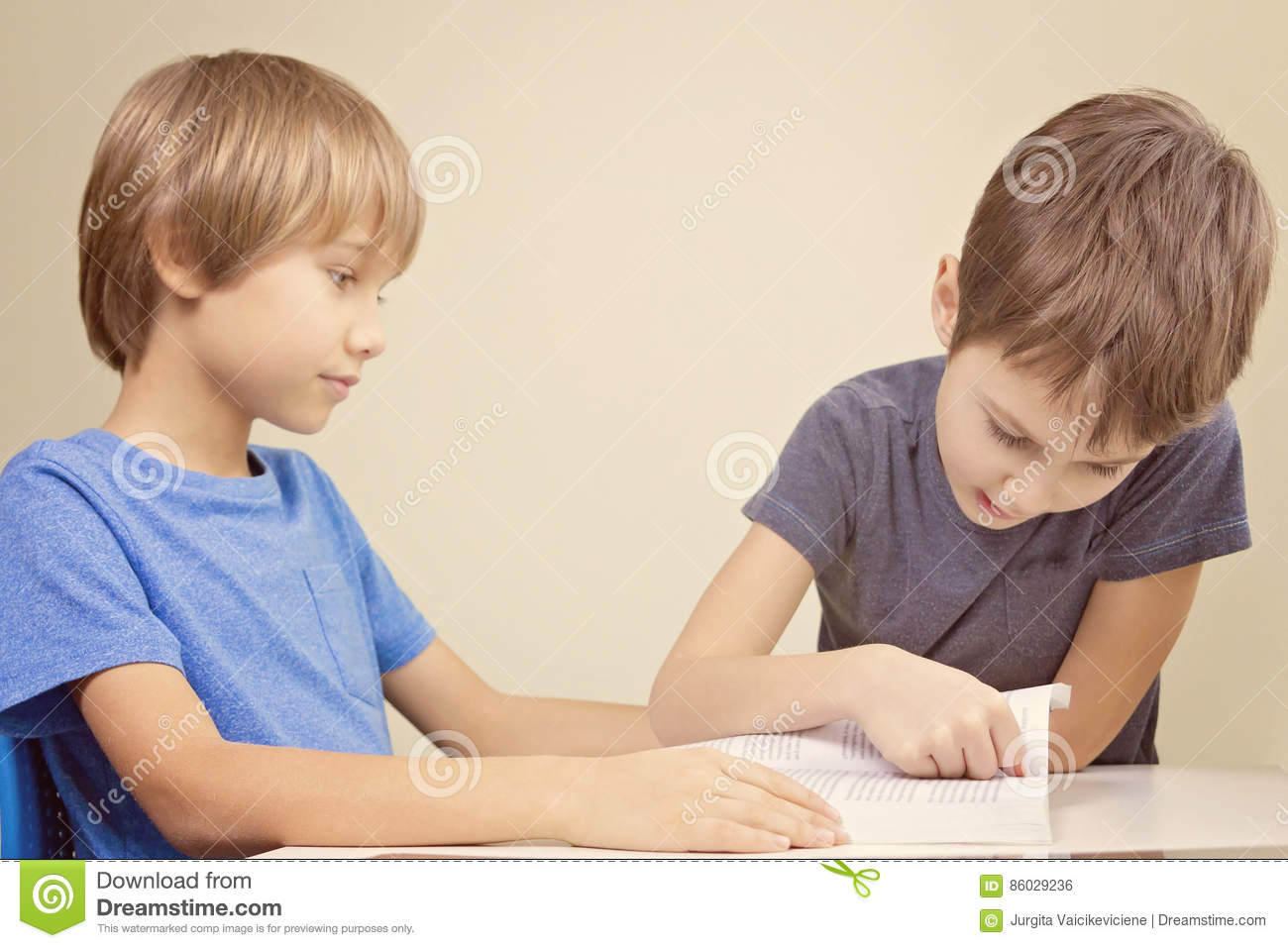 Kids reading a book. Little boy practice reading with his brother.