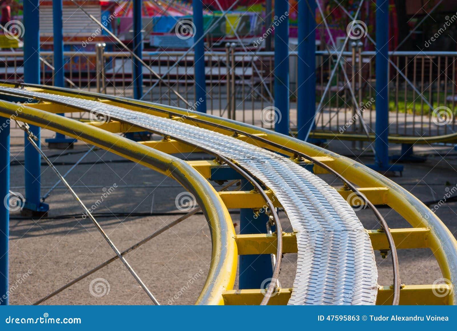 Kids roller coaster yellow rails in amusement park.