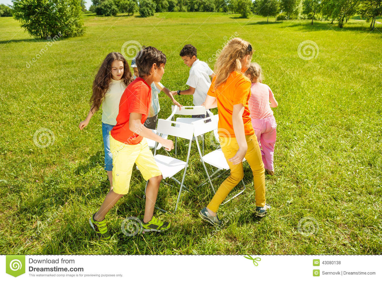 Kids run around playing musical chairs game stock photo for Chaise game free download