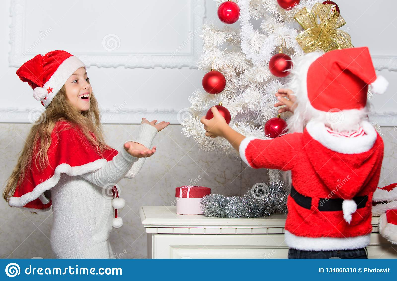 Christmas Hats For Kids.Kids In Santa Hats Decorating Christmas Tree Family