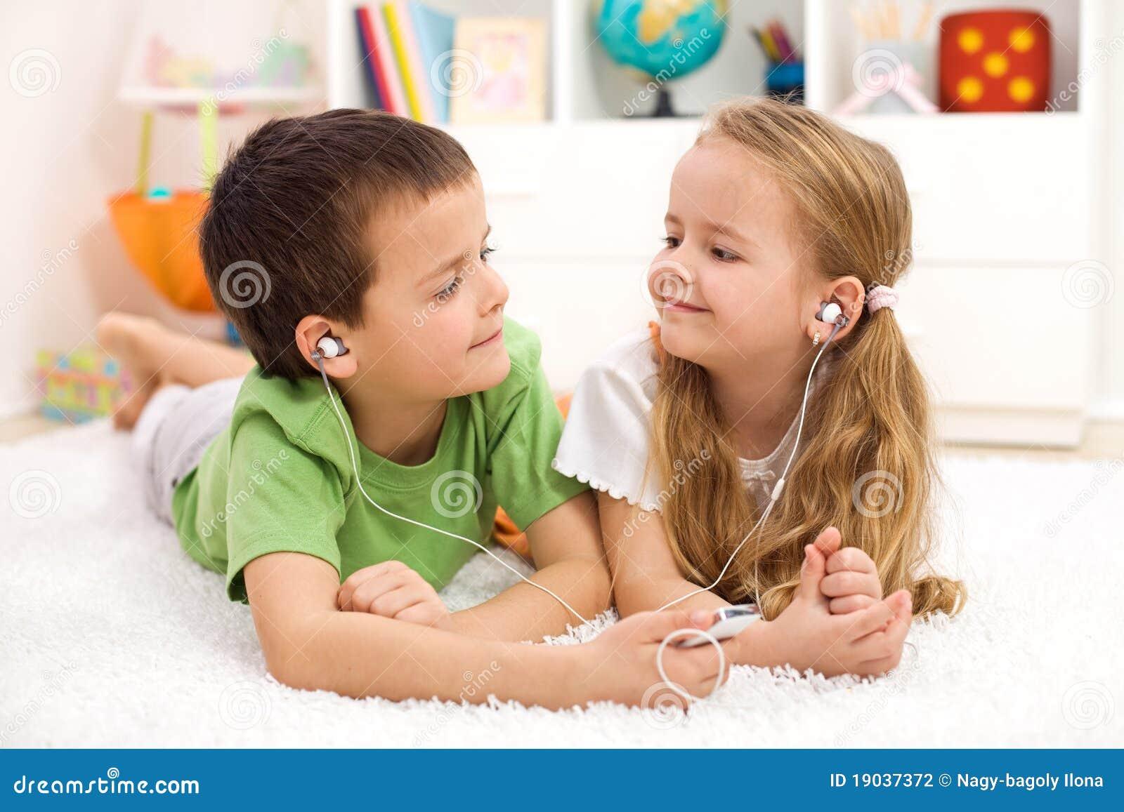 Kids sharing earphones listening to music