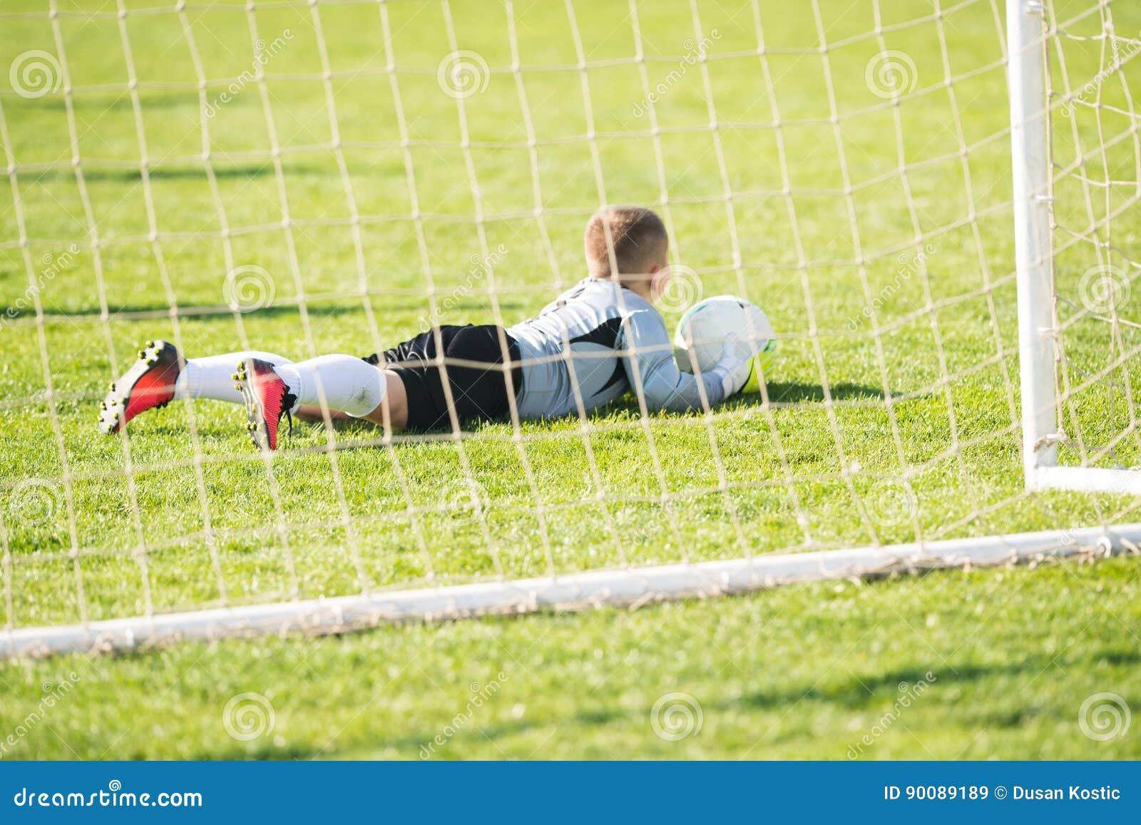 Kids soccer football - goal keeper on the match on soccer field