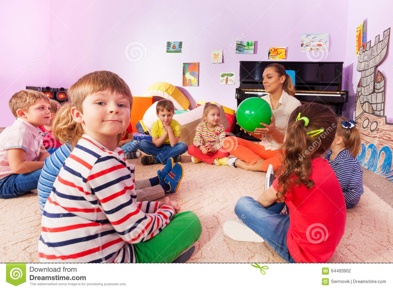 Kinder Garden: Kids And Teacher Sit In Circle Stock Photo