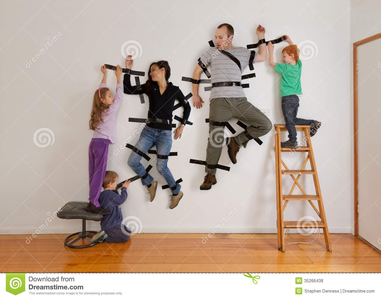 Kids Teamwork Taping Parents To Wall Royalty Free Stock