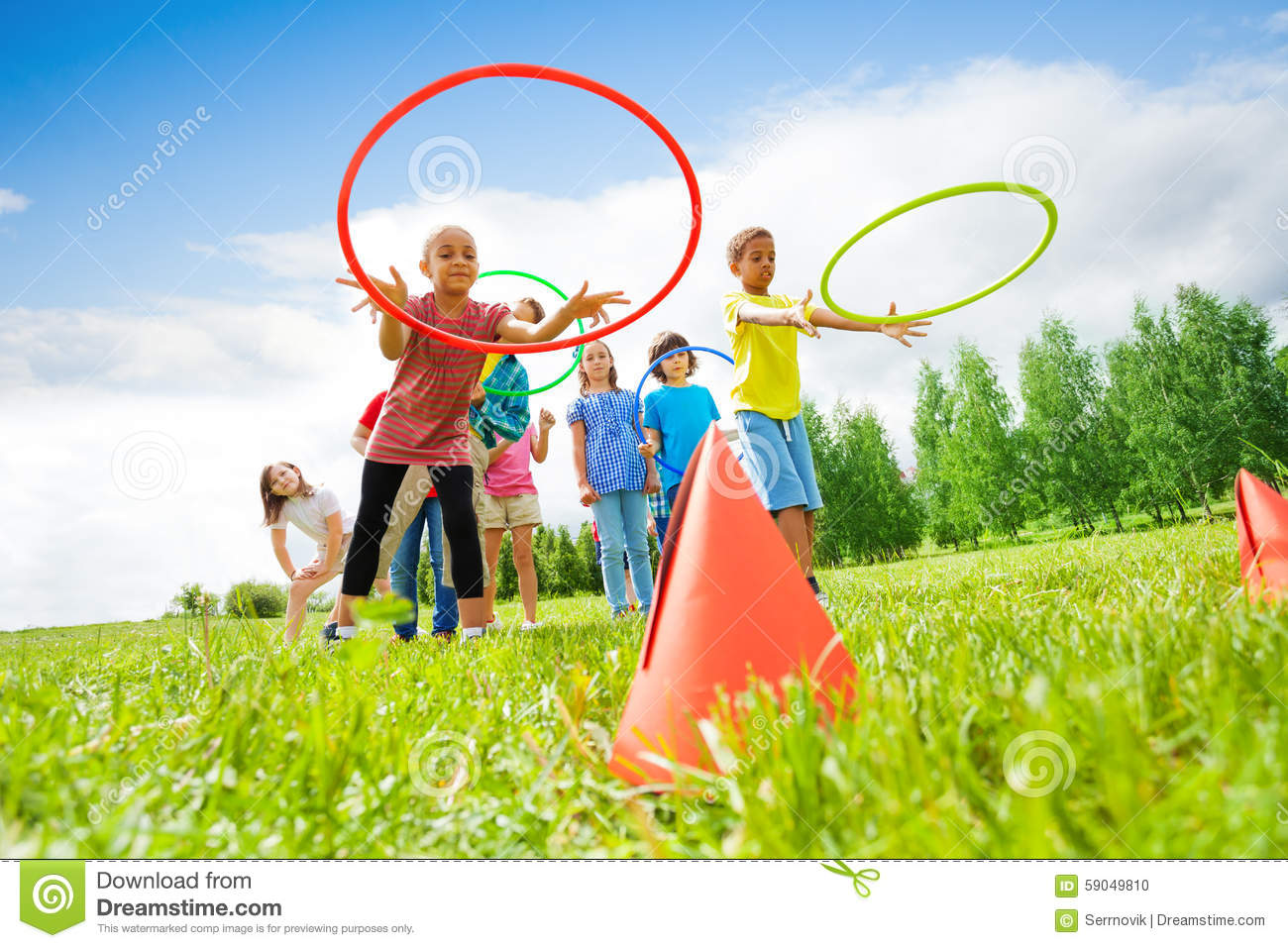 Kids Throw Colorful Hoops On Cones While Competing Stock