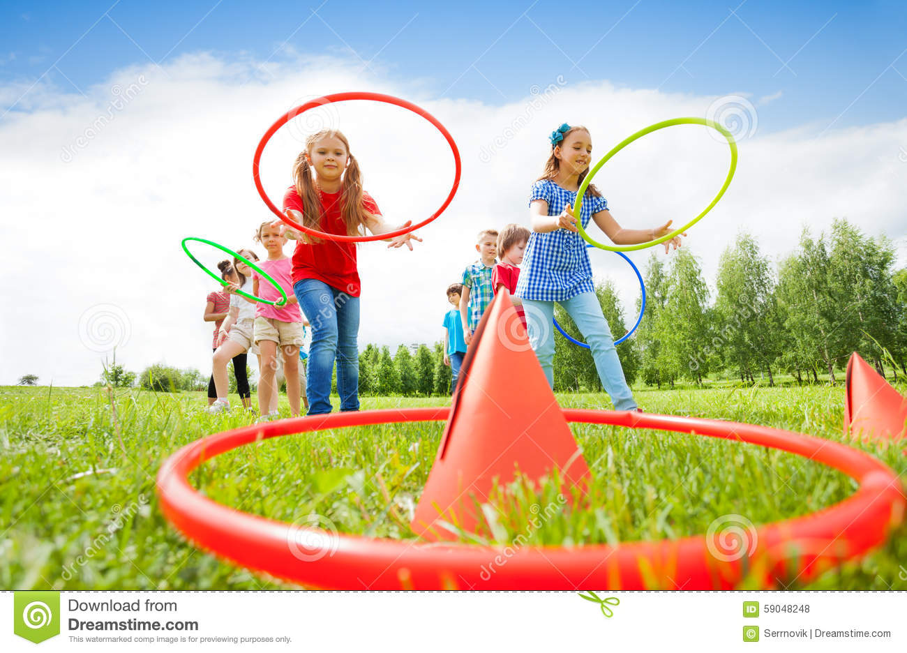 kids throw colorful hoops on cones while competing stock. Black Bedroom Furniture Sets. Home Design Ideas