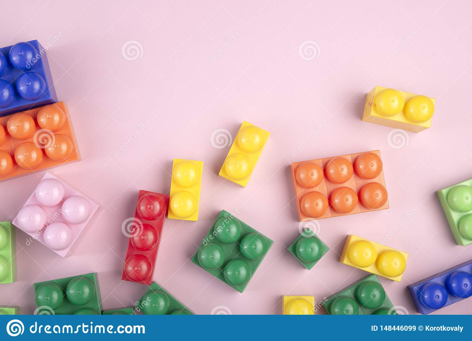 Kids toys background with colorful blocks laying on the pink table. Copy space for text