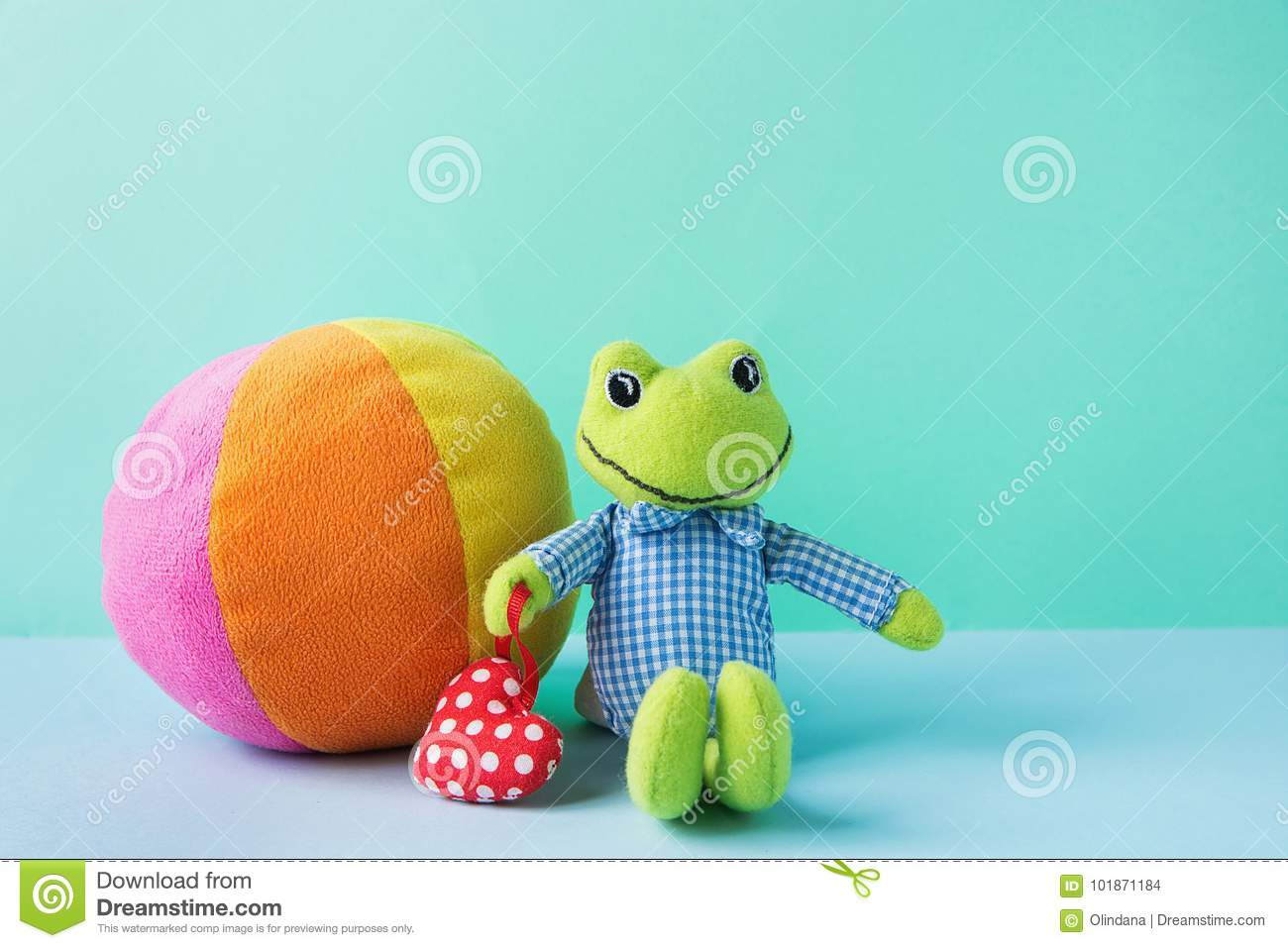 Kids Toys Small Plush Frog Holding Red Heart Multicolored Textile Soft Ball on Blue Green Background. Banner Placeholder Charity