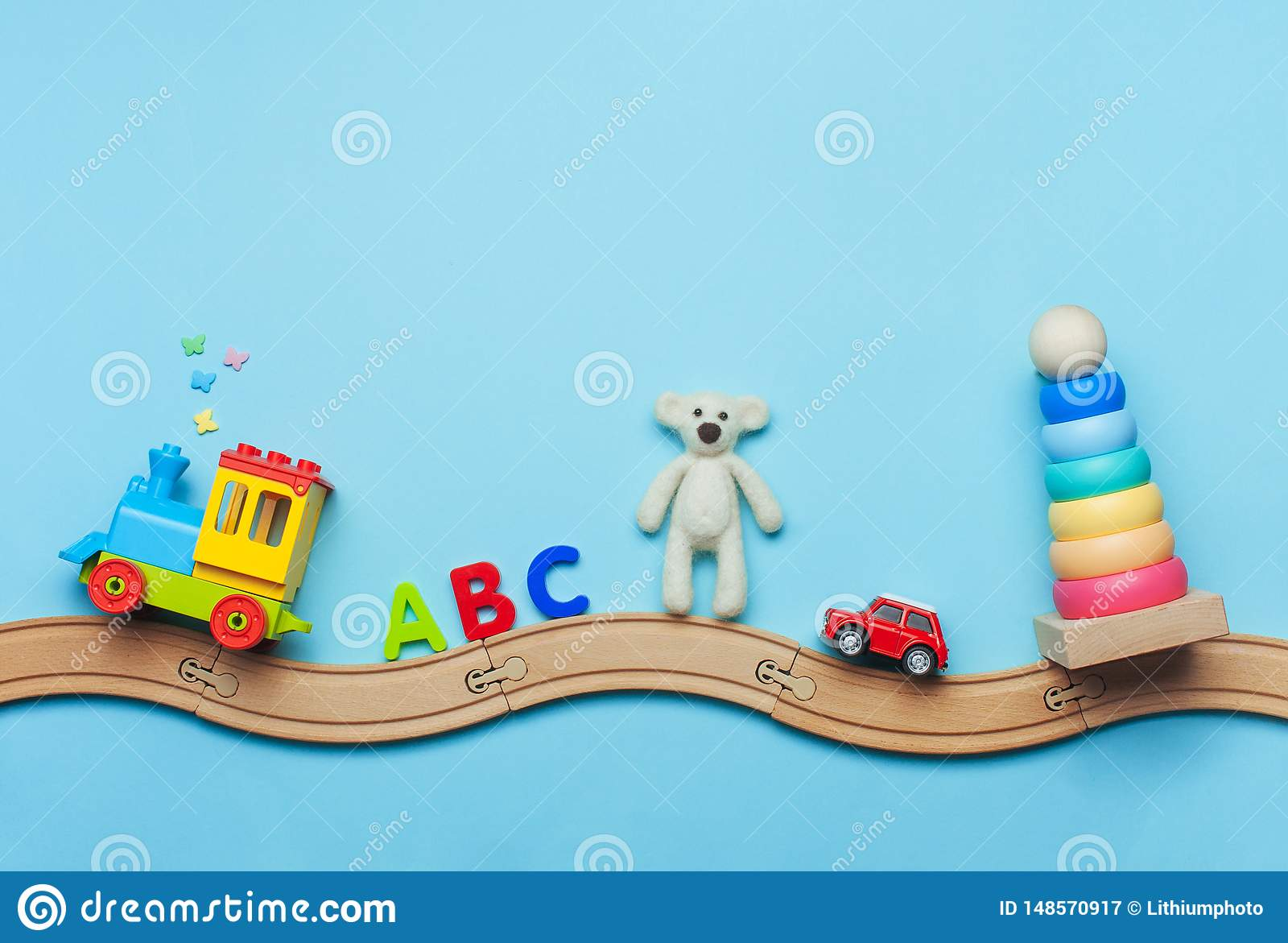 Kids Toys On Wooden Railway On Blue Background With Copy Space Stock