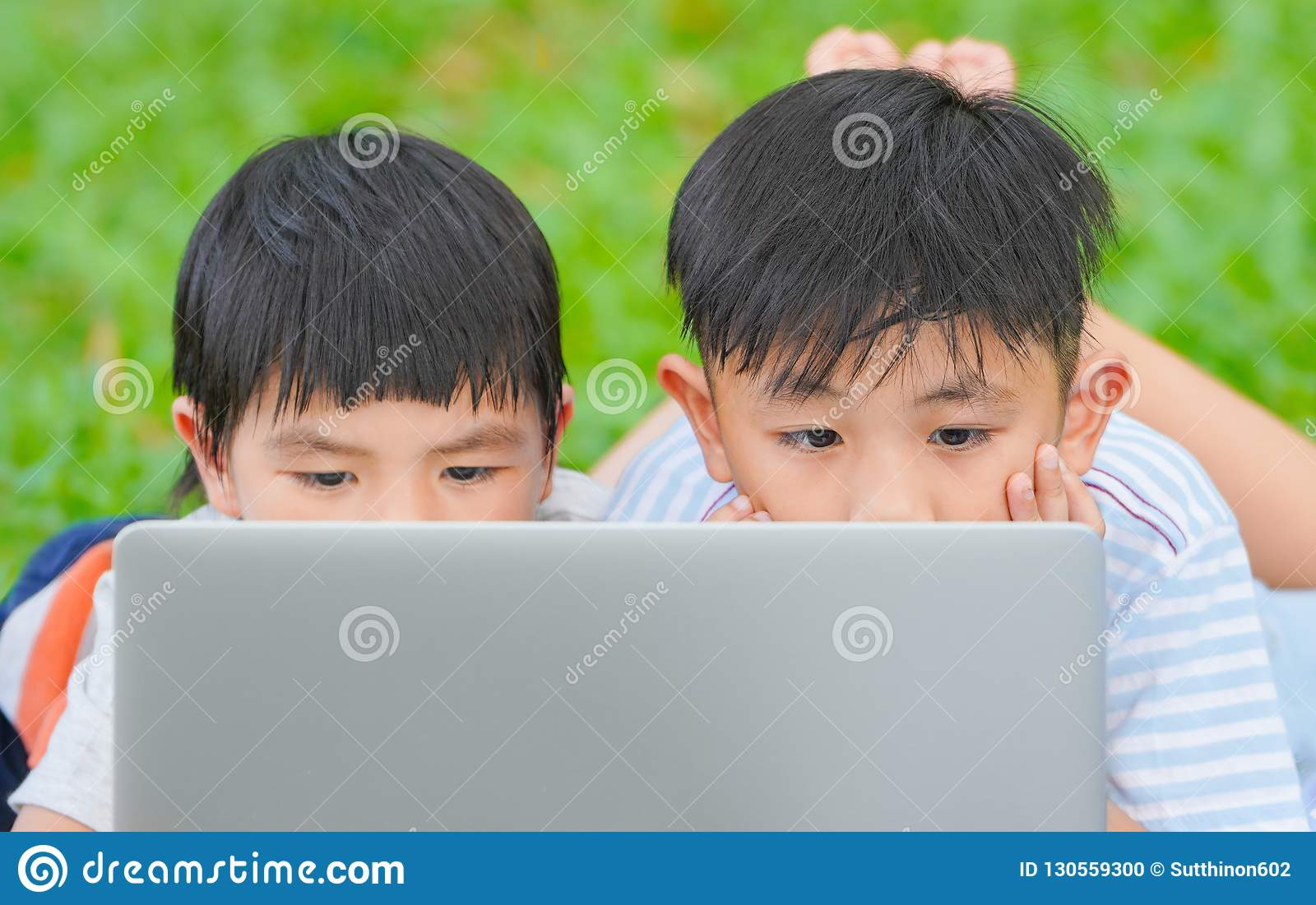 Kids using laptop, Summer school concept, Asian children are playing laptop computer in the park.