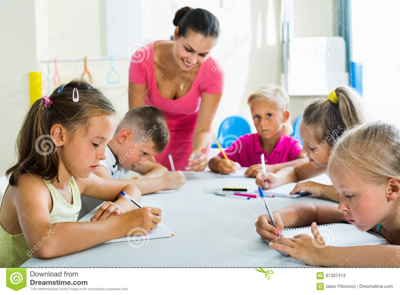 kids writing together with tutor at school class stock image - image