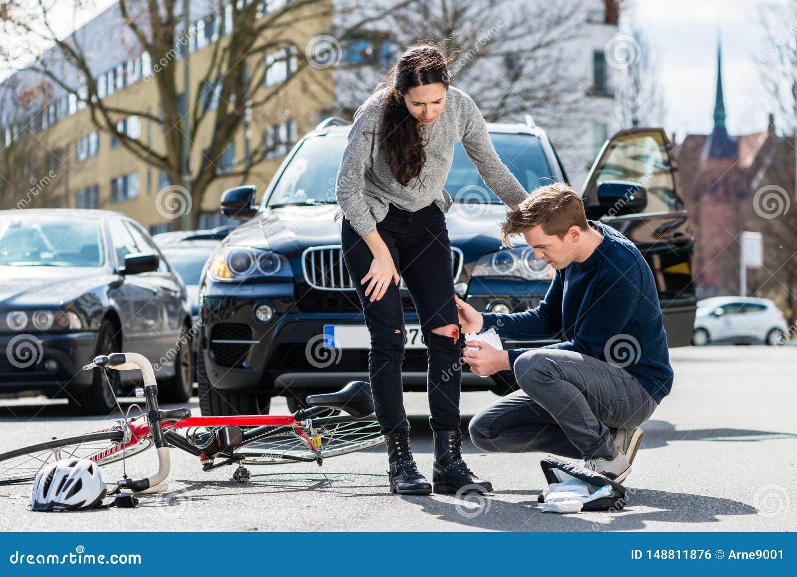 Kierowca używa bezpłodnego bandaż pomagać zdradzonego bicyclist