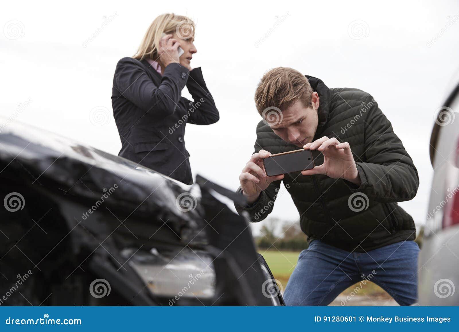 Kierowcy Bierze fotografię wypadek samochodowy Na telefonach komórkowych