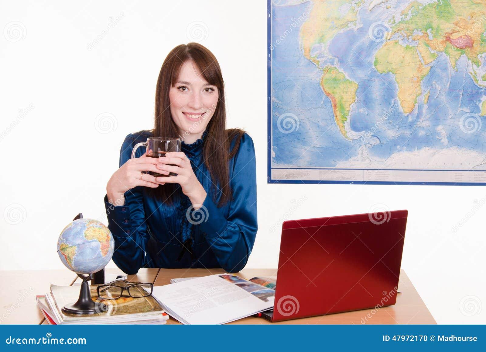Kierownik agencja podróży pije herbaty w miejscu pracy