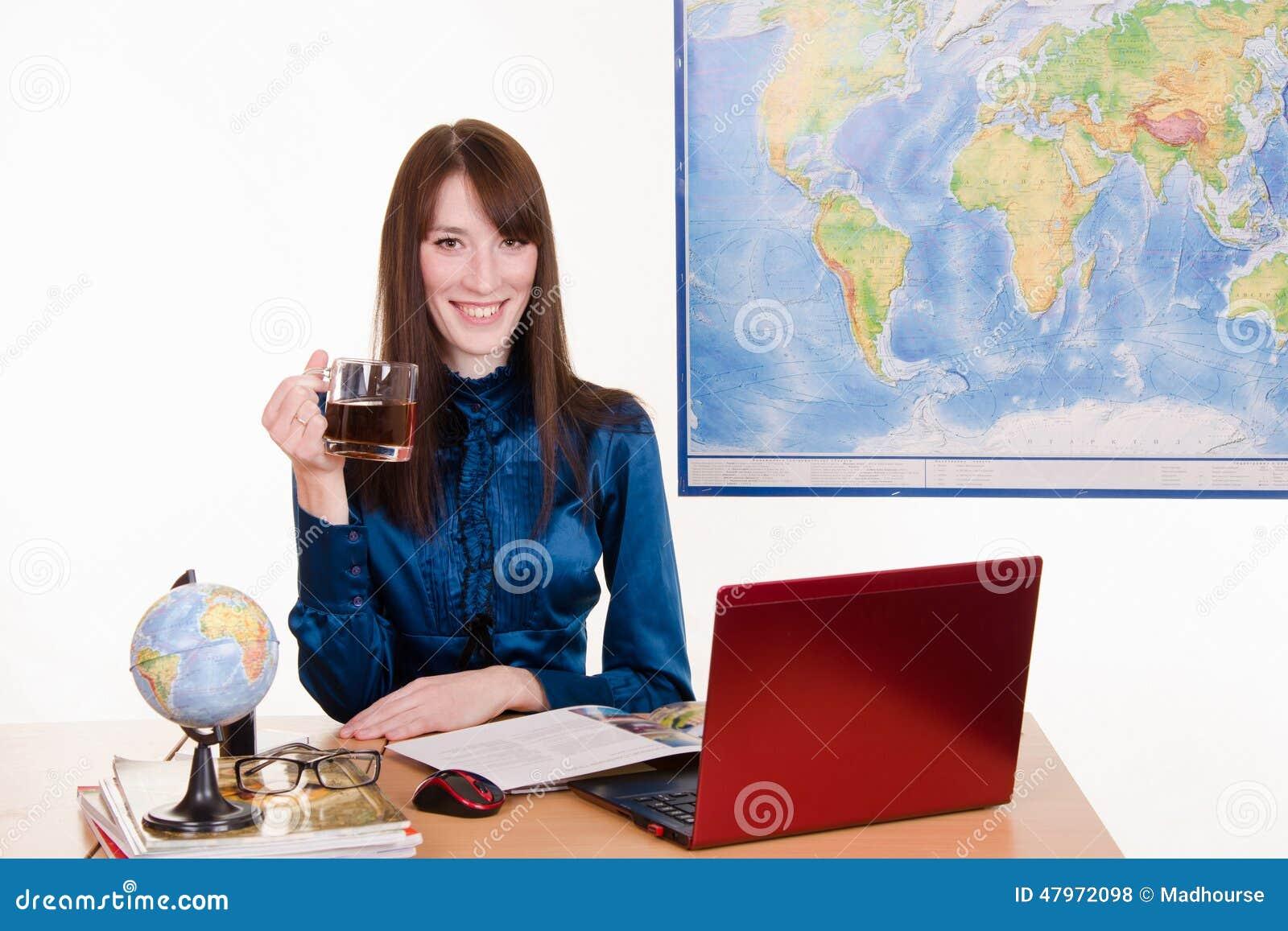 Kierownik agencja podróży z kubkiem herbata w ręce