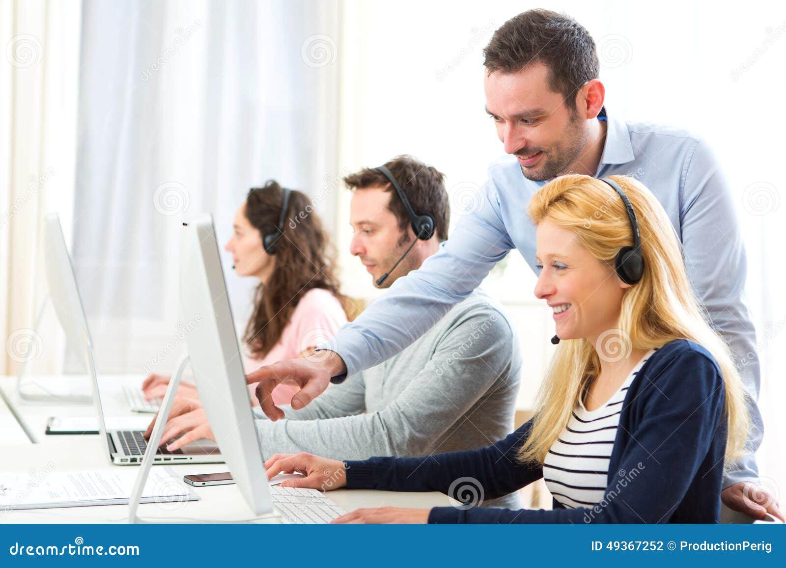 Kierownika trenować młodzi atrakcyjni ludzie na komputerze