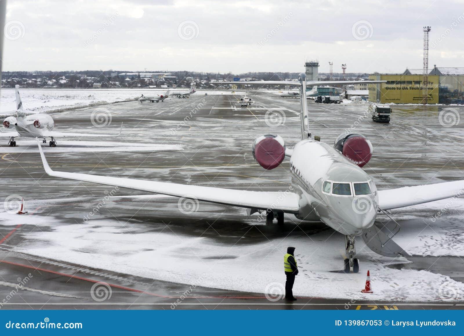 Kiev, de Oekraïne, Februari 2019 Vliegtuigen, de baan, de arbeiders - de gebruikelijke wijze van verrichting van de luchthaven Ki