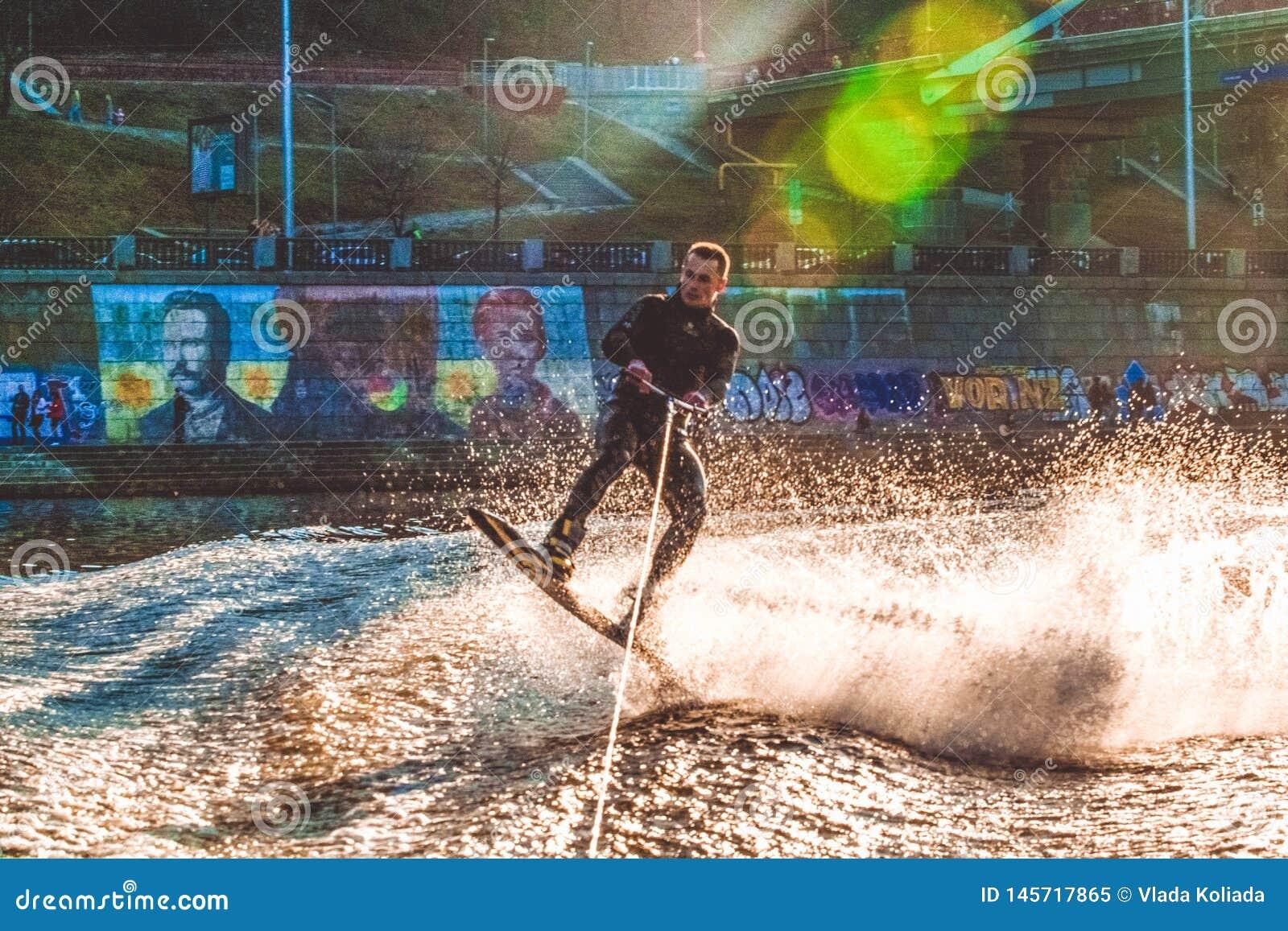 Kiev, de Oekra?ne 31 03 2019 De kerel in een thermosuit berijdt een raad op water in de lokale rivier Moderne sport Wakeboarding