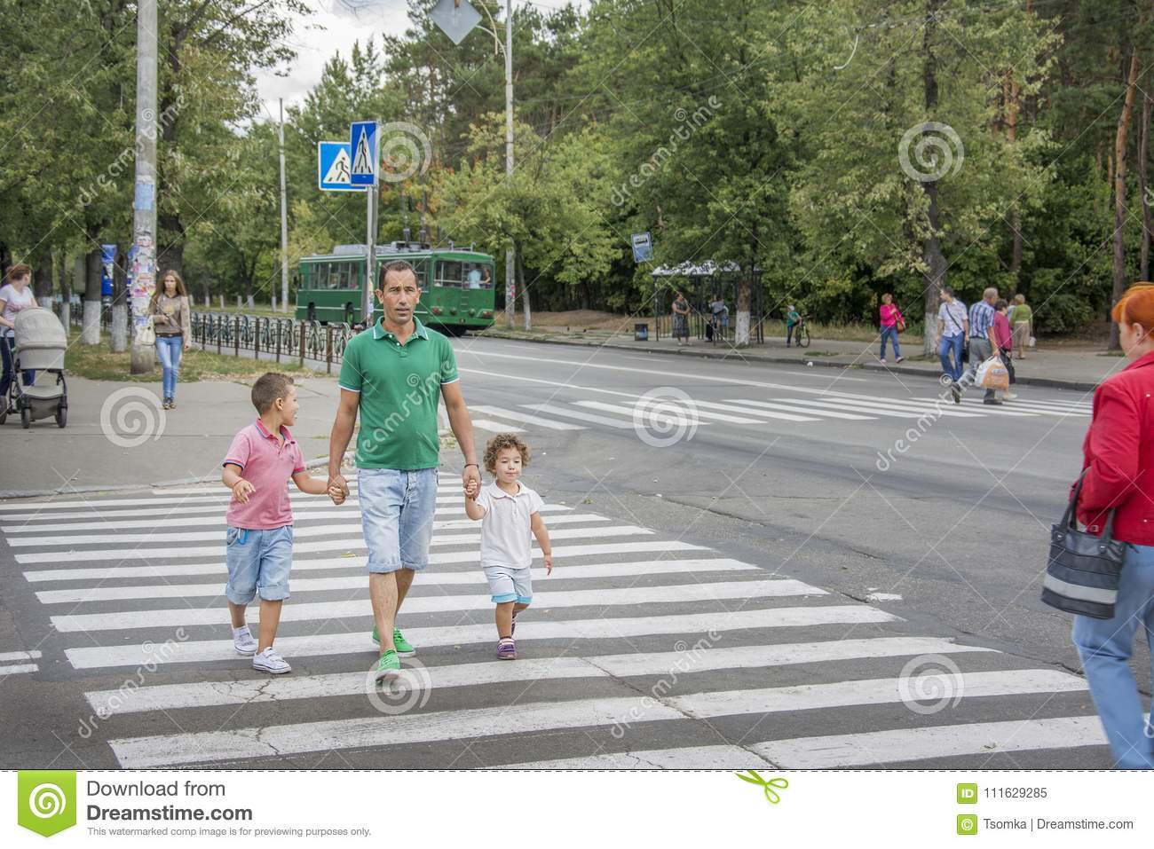 Kiev. In summer, at the pedestrian crossing, the father and children cross the road.