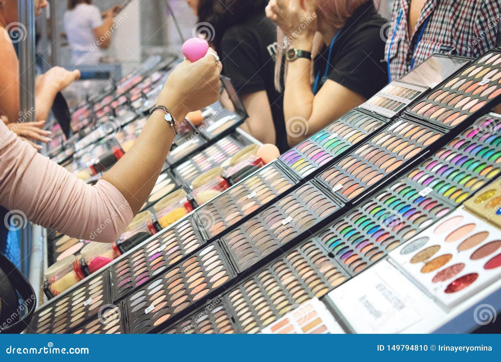 Kiev, Ucrânia 19 de setembro de 2018: A jovem mulher escolhe cosméticos decorativos no suporte da loja da beleza durante a mostra