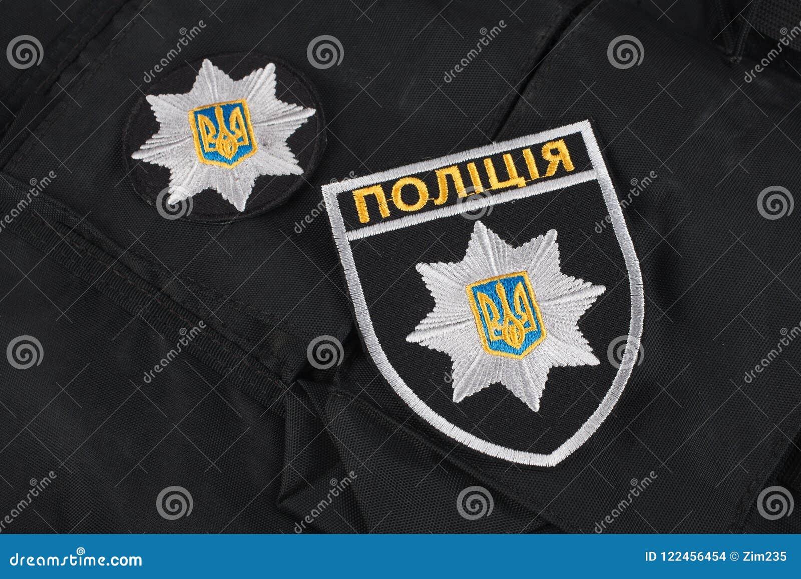 KIEV, UCRÂNIA - 22 DE NOVEMBRO DE 2016 Remendo e crachá da polícia nacional de Ucrânia no fundo uniforme preto