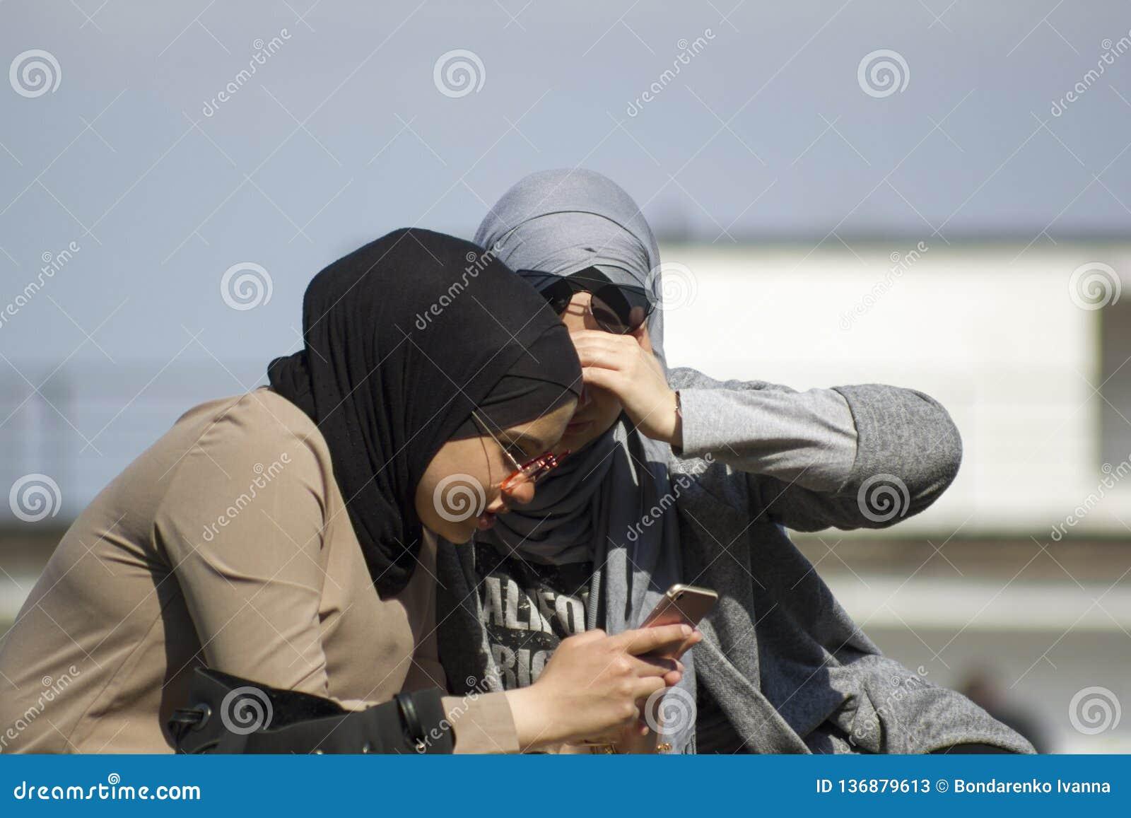 Kiev Ucrania - 21 de abril de 2018: dos mujeres musulmanes jovenes en los vidrios de sol que miran en smartphone