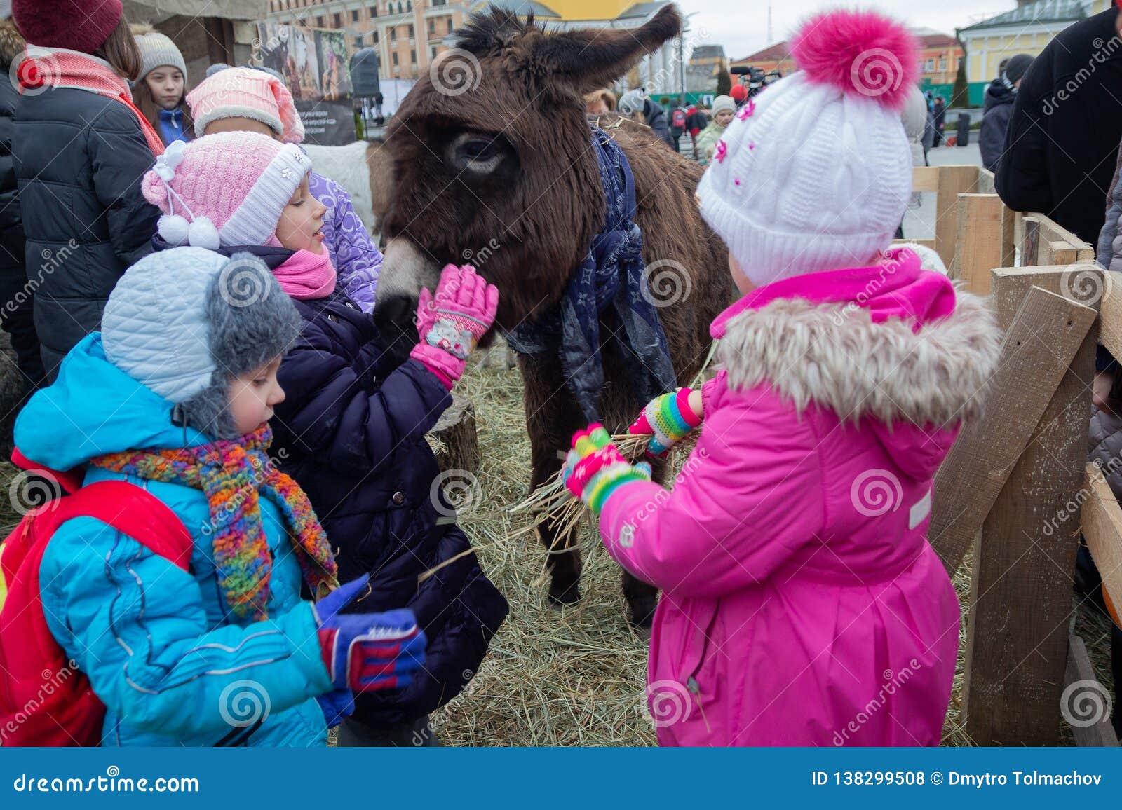 Kiev, Ucrania - 13 de enero de 2018: Animales de la alimentación de los niños en el parque zoológico