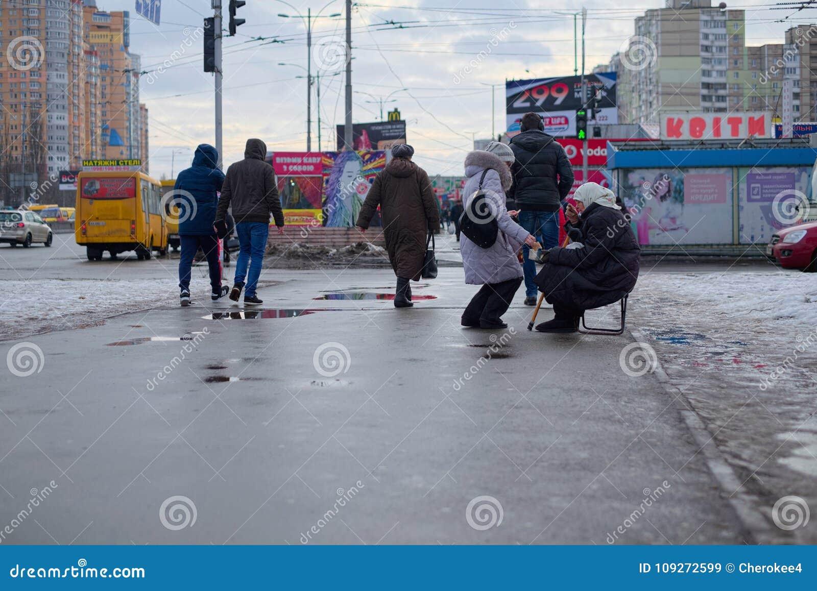 KIEV UKRAINA - JANUARI 29, 2018: En gammal hemlös kvinnatiggeri En fattig tiggeri för gammal kvinna på gatan