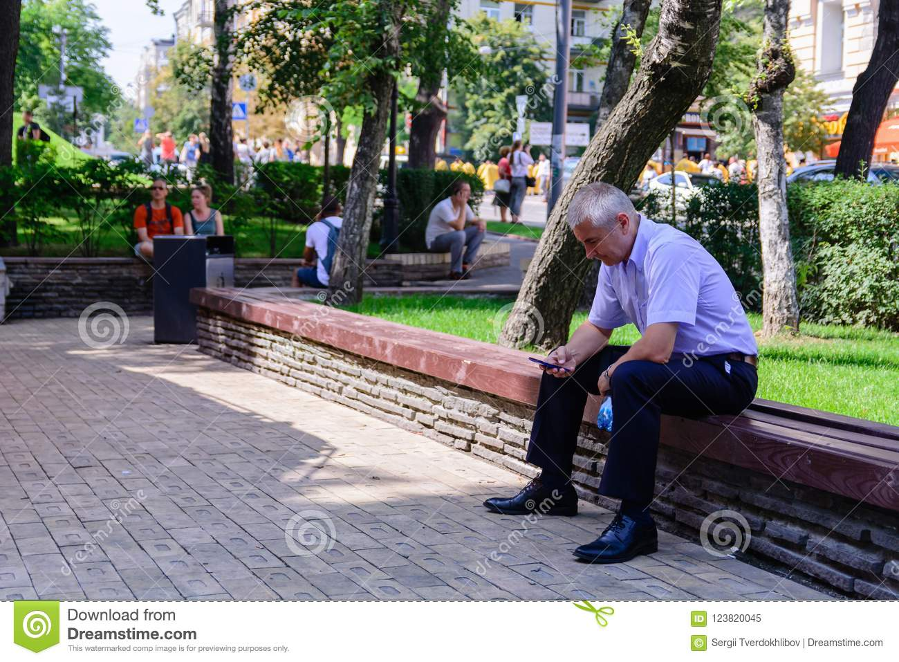 KIEV, UKRAINE - 20 JUNE 2018: man texting with his mobile phone, he is sitting on a wooden bench