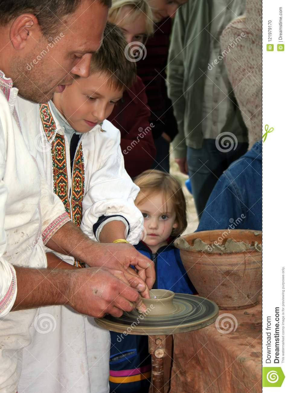 Kiev, Ukraine, 08.10.2005. The potter is teaching children the art of pottery