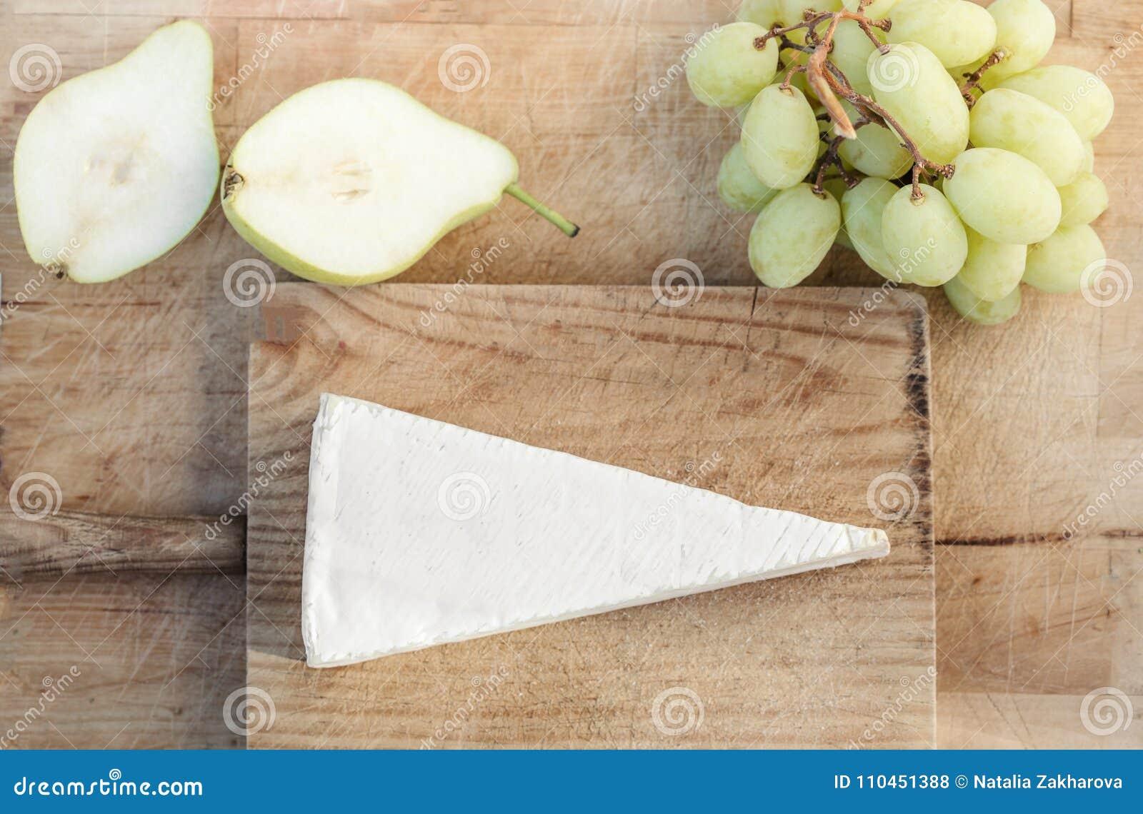 Kil av Brie på lantlig vit träbackeround vit s