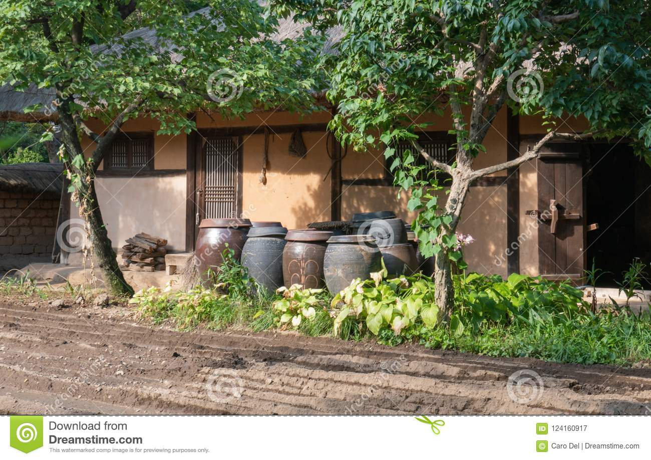 Kimchi Jars In Front Of Korean Traditional House With Wooden Door And Garden
