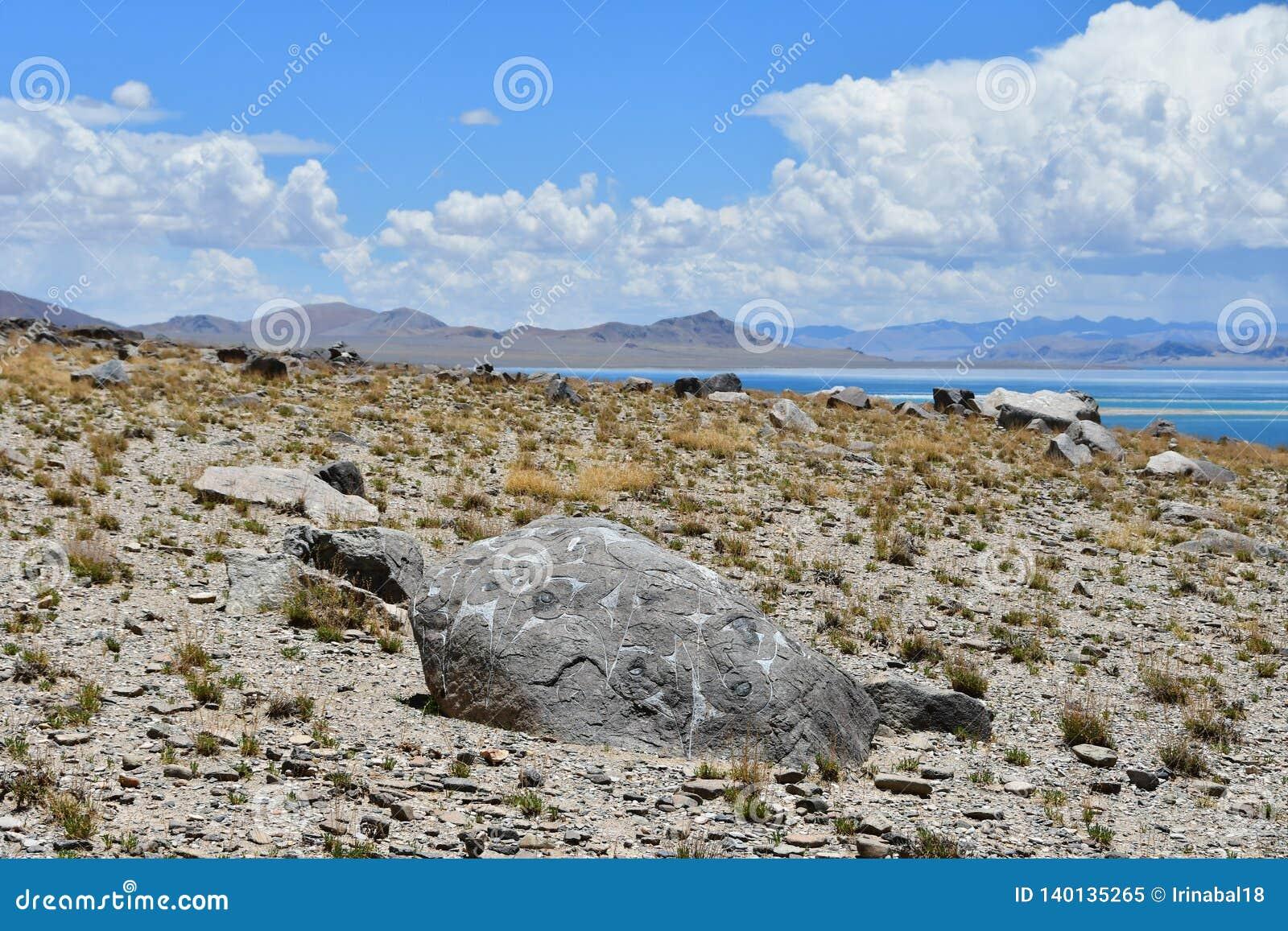 Kina Great Lakes av Tibet Sten med mantras på lagret av sjön Teri Tashi Namtso i solig sommardag