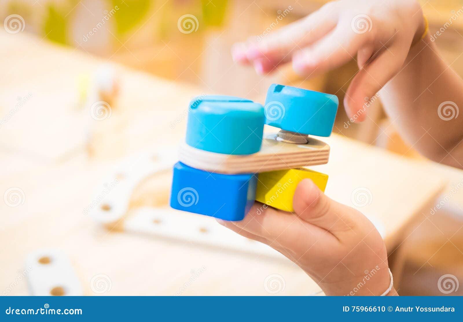 Kind übergibt das Errichten eines Bildungswarenkorbes hölzerner Bauklotz