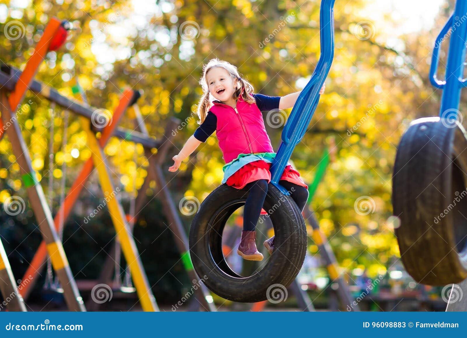 Kind auf Spielplatz im Herbst Kinder im Fall