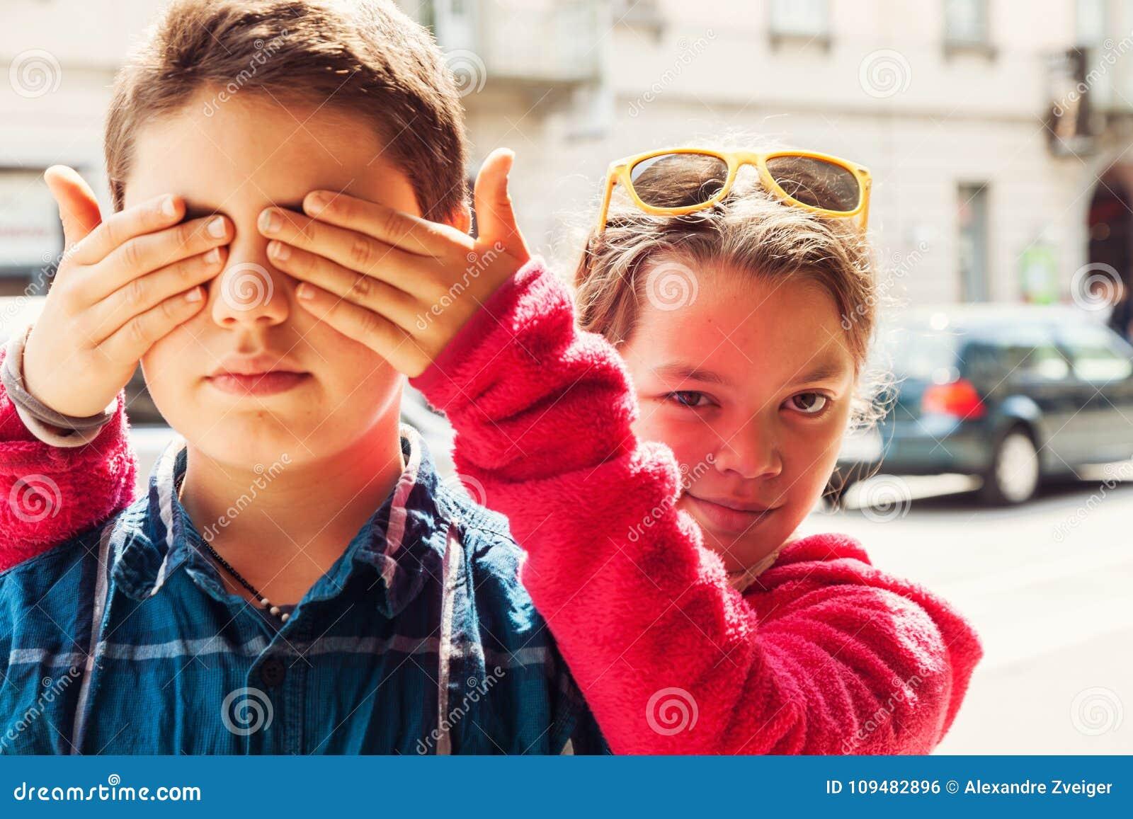 Kind bedeckt seine Augen mit seinem Bruder, Porträt