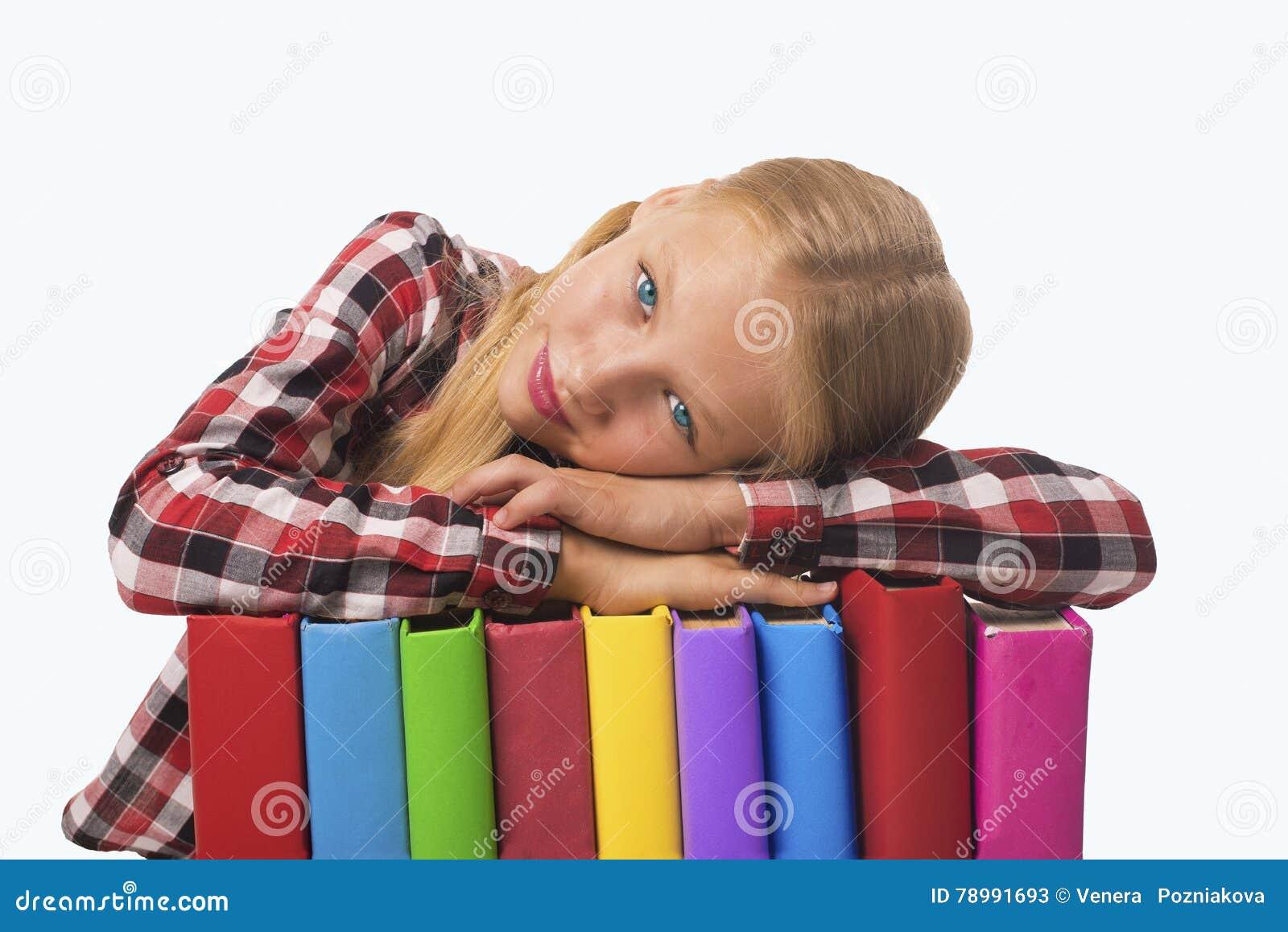 Kind, das auf Stapel der Bücher liegt