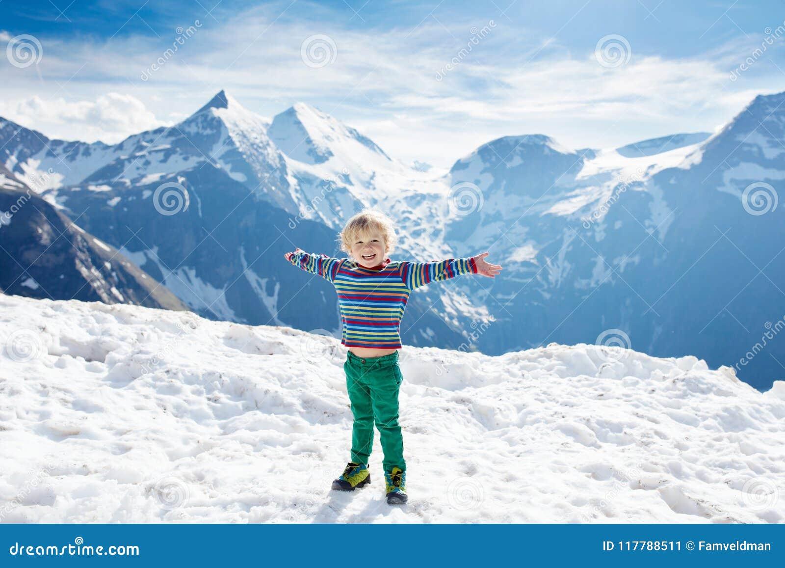 Kind, das in den Bergen wandert Kinder im Schnee im Frühjahr