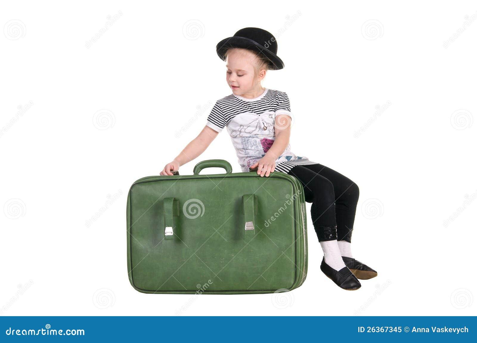 Kind, das in einem alten grünen Koffer sitzt