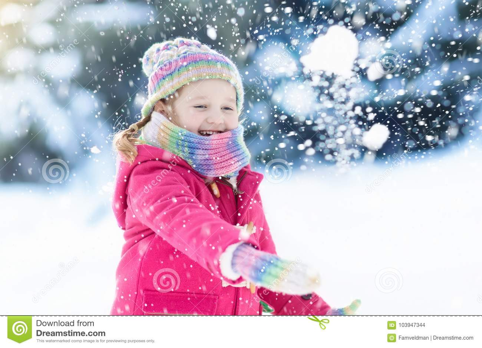 Kind, das mit Schnee im Winter spielt Kinder draußen