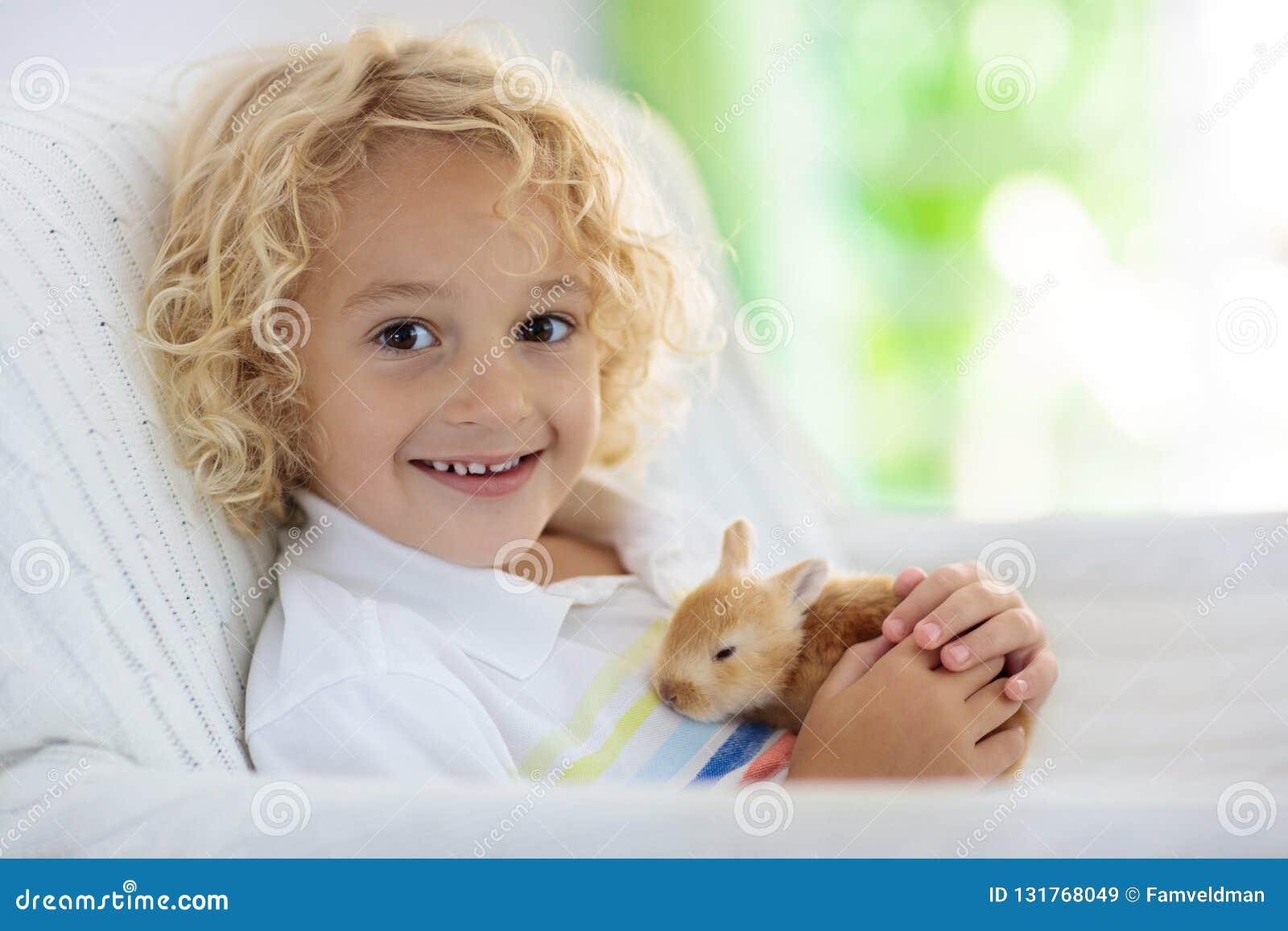 Kind, das mit weißem Kaninchen spielt Kleiner Junge, der weißes Häschen einzieht und streichelt Ostern-Feier Eijagd mit Kinder- u
