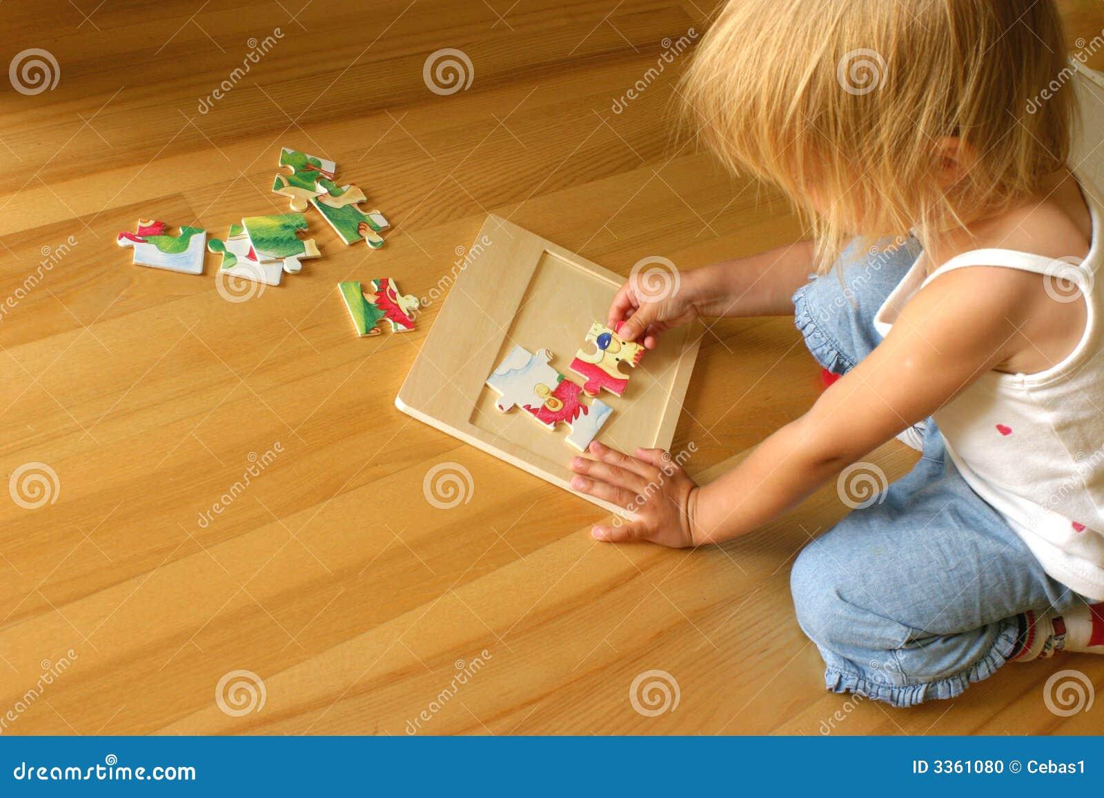 Kind, das Puzzlespiel löst
