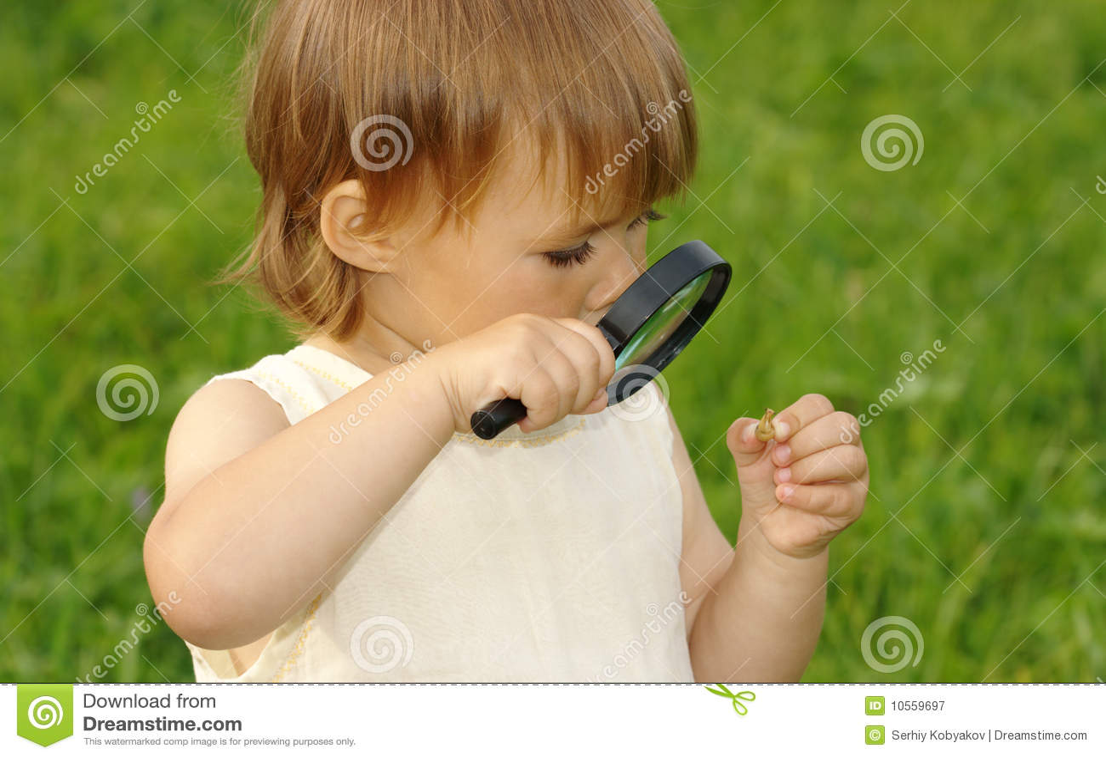 Kind, das Schnecke durch Vergrößerungsglas betrachtet