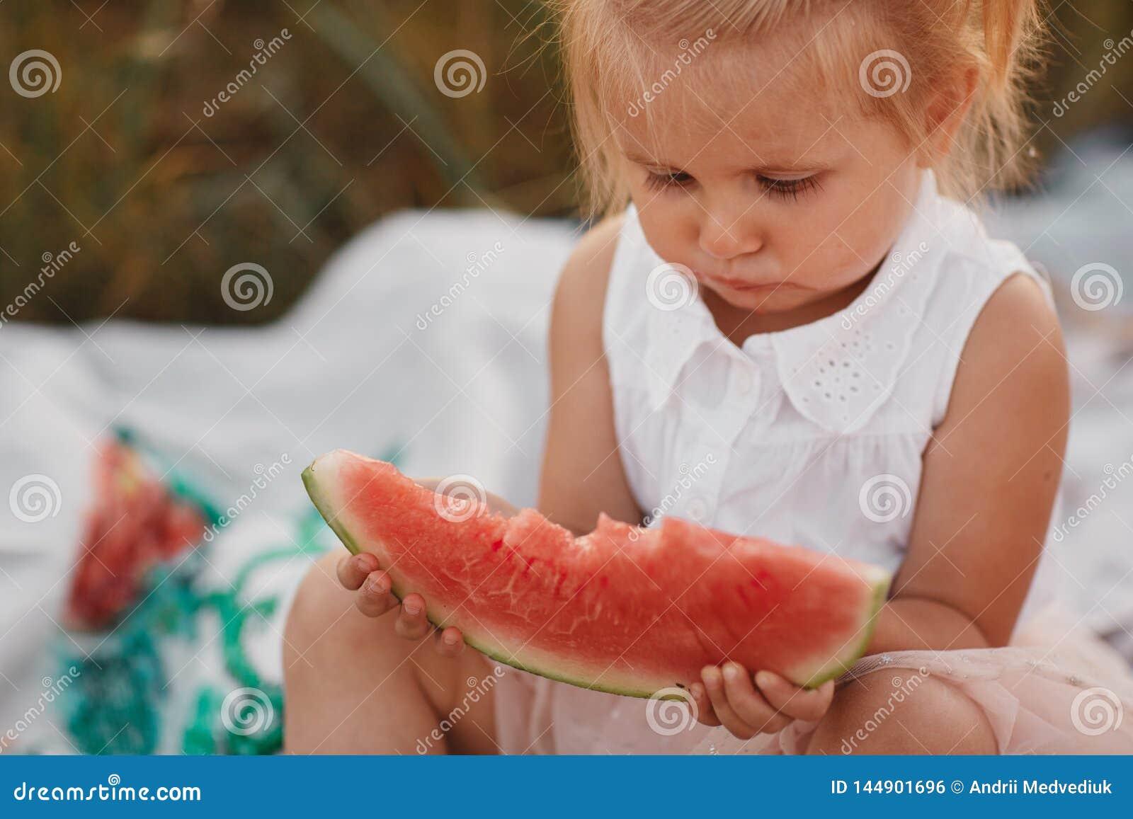 Kind, das Wassermelone im Garten isst Kleines M?dchen, das im Garten h?lt eine Scheibe der Wassermelone spielt Kindergartenarbeit