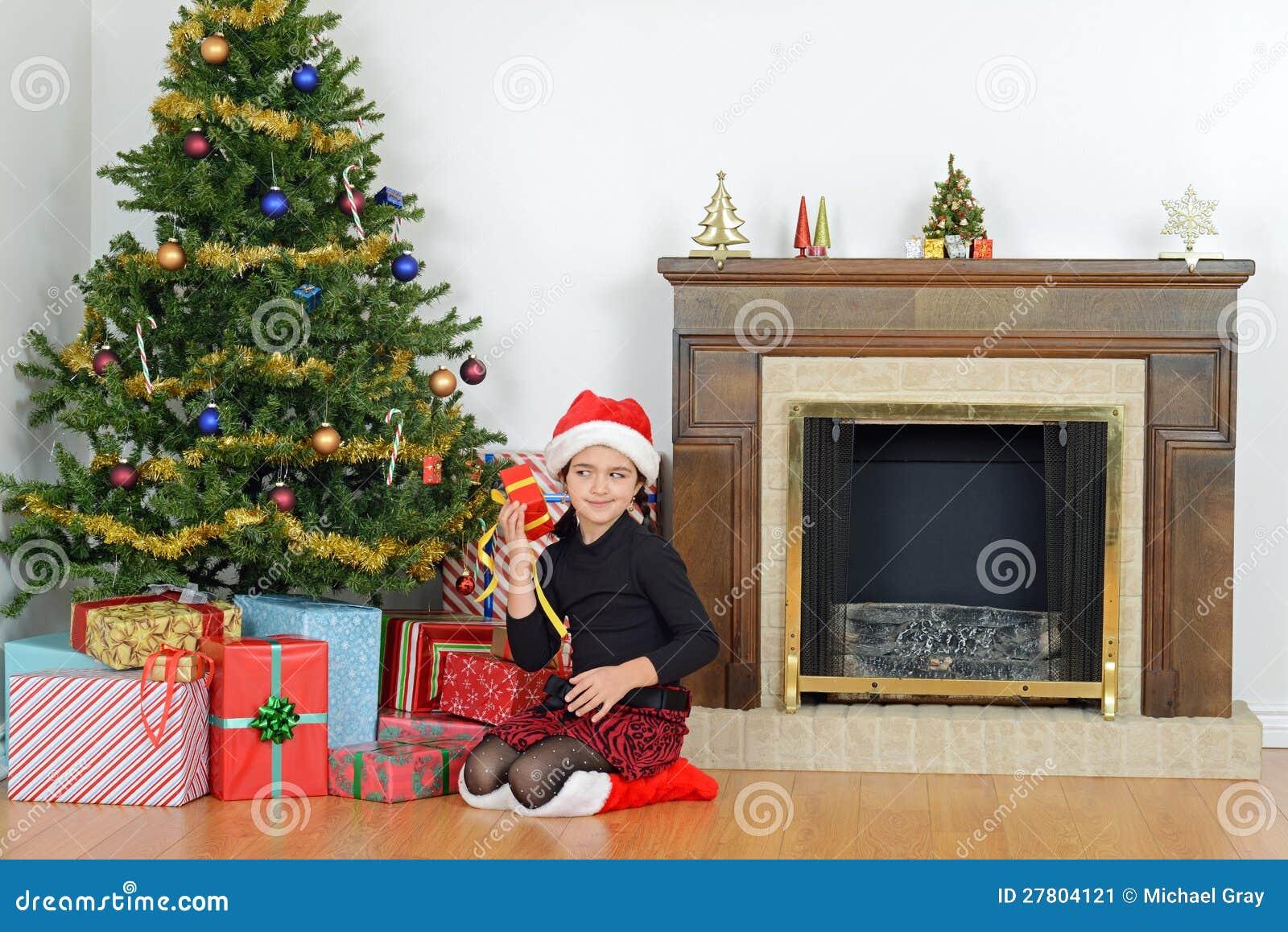 kind das weihnachtsgeschenk durch baum r ttelt stockbild. Black Bedroom Furniture Sets. Home Design Ideas