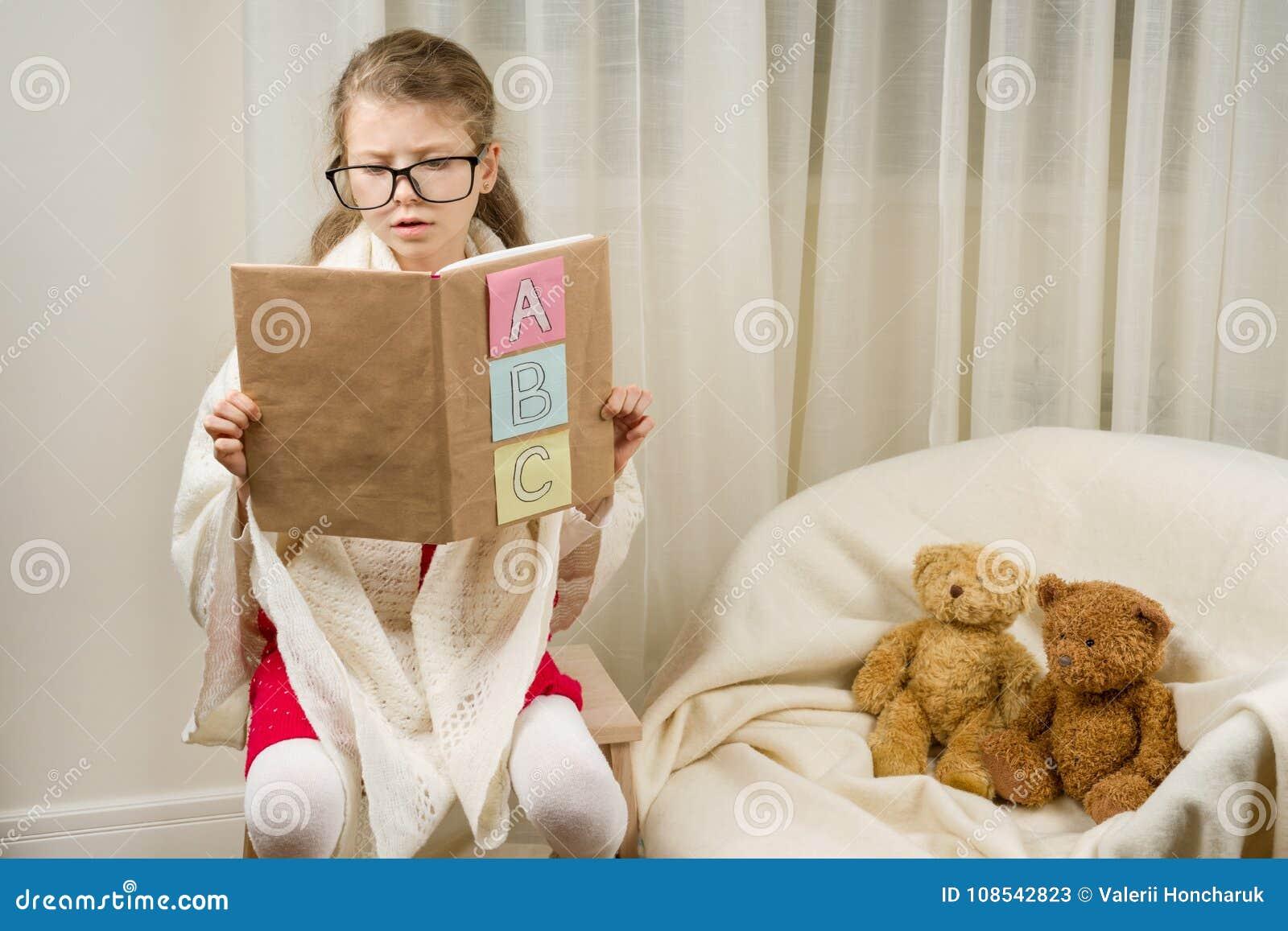 Kind, das zu Hause Schullehrer mit Teddybären spielt