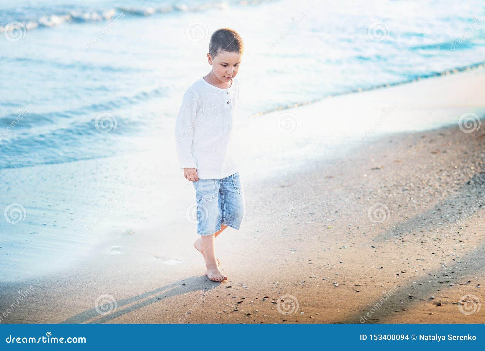 Kind dat op het strand loopt De vakantie van de zomer het gelukkige jong geitje spelen op strand in de zonsondergangtijd