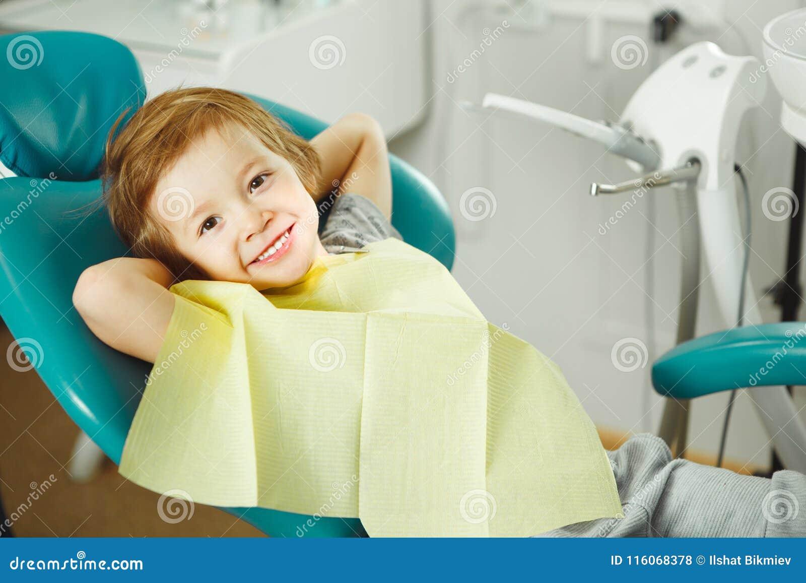 Kind in der guten Laune, die auf Stuhl und ohne Furchtwartezahnarzt Jungen sitzt, wird Zähne behandeln karies