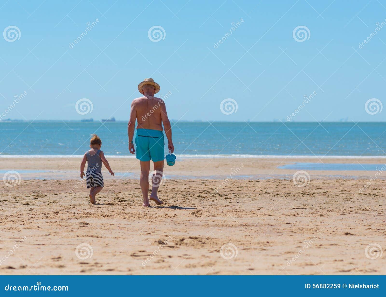 Kind des kleinen Jungen mit Großvater auf dem Strand