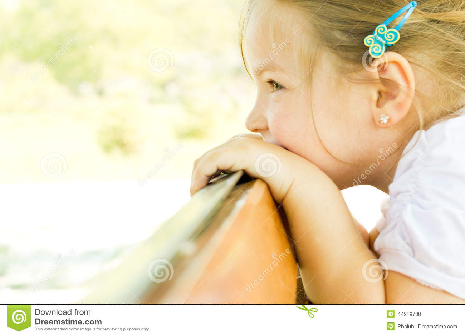 Kind des kleinen Mädchens, das über einem Geländer schaut